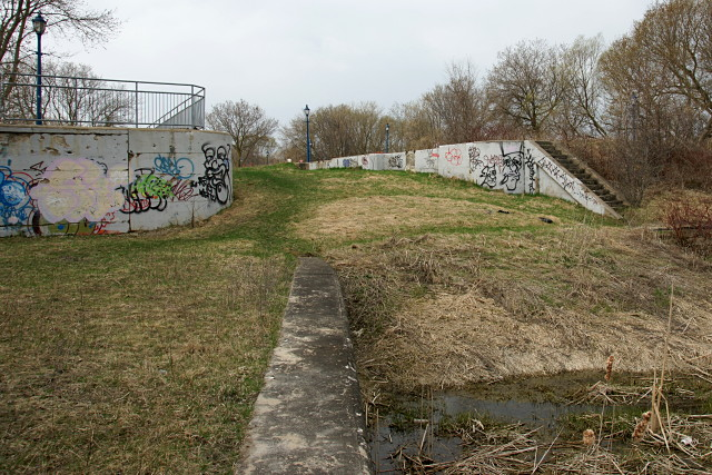 The highest lock on the canal has been filled in. A recreational trail crosses the top of the lock structure and continues at the left of the picture where the guardrail is.