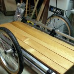 The oak slats, dry after a third coat of Varathane, get a dry fit before being secured to the trailer frame.