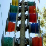 Colourful spools of cable await deployment along a line of utility poles