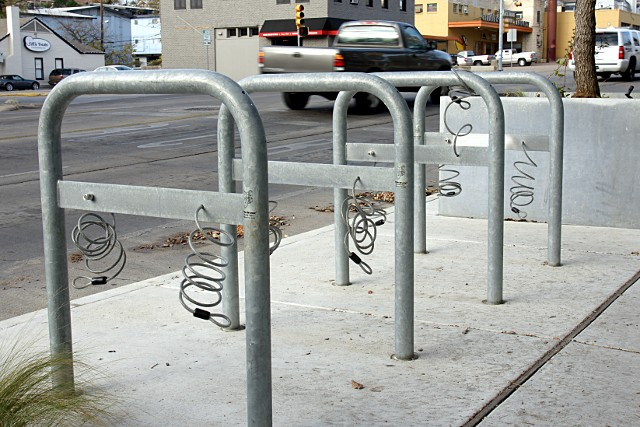 Bike racks with integrated cable locks