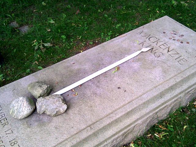 Thirteen pennies on Mackenzie King's grave marker