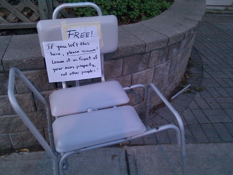 Sign on a chair left at the curb