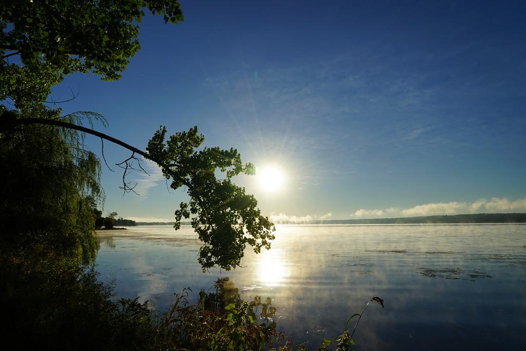A rising sun burns the fog off Rice Lake